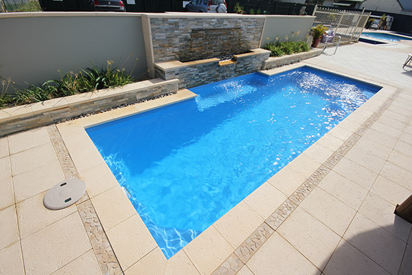 """Chateau"" Fibreglass Swimming Pool Design, pictured with water feature in backyard"