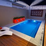 """Empire"" Indoor Fibreglass Swimming Pool Design, with water feature and surrounded by decking"