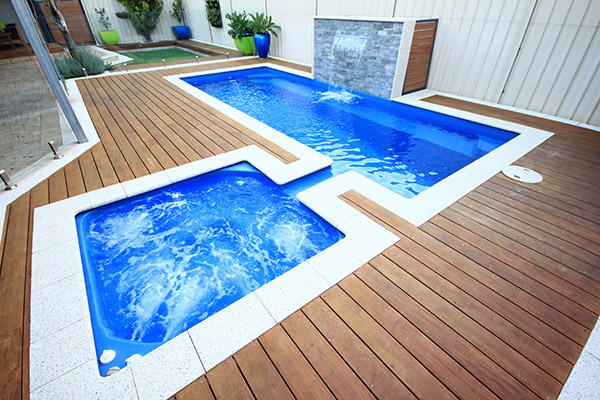 """Florentina"" Fibreglass Swimming Pool Design, pictured with water feature in backyard with decking"